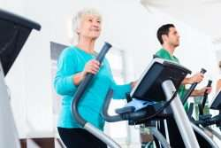 Older woman in blue working out on Elliptical Machine