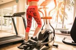 Female in pink athletic pants on the Elliptical Machine