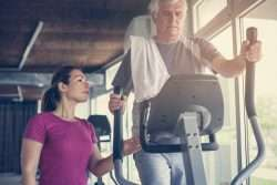 Trainer working with man on Elliptical Machine
