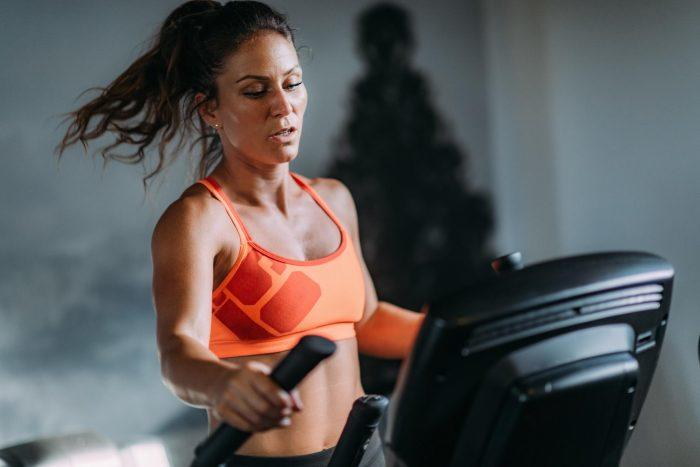 women in ponytal and sports bra on elliptical machine