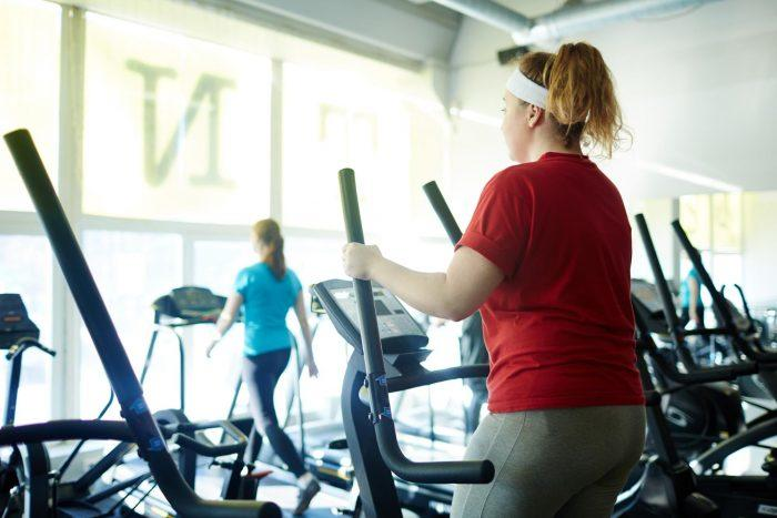 female on reed shirt on elliptical machine